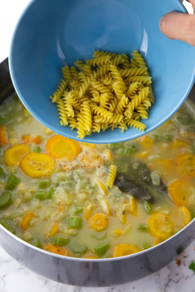 uncooked rotini pasta in a blue bowl are being poured into a pot of vegan chicken noodle soup