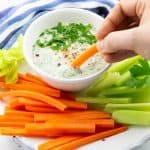 a hand dipping a carrot stick in a small bowl of vegan ranch on a plate with carrot and celery sticks