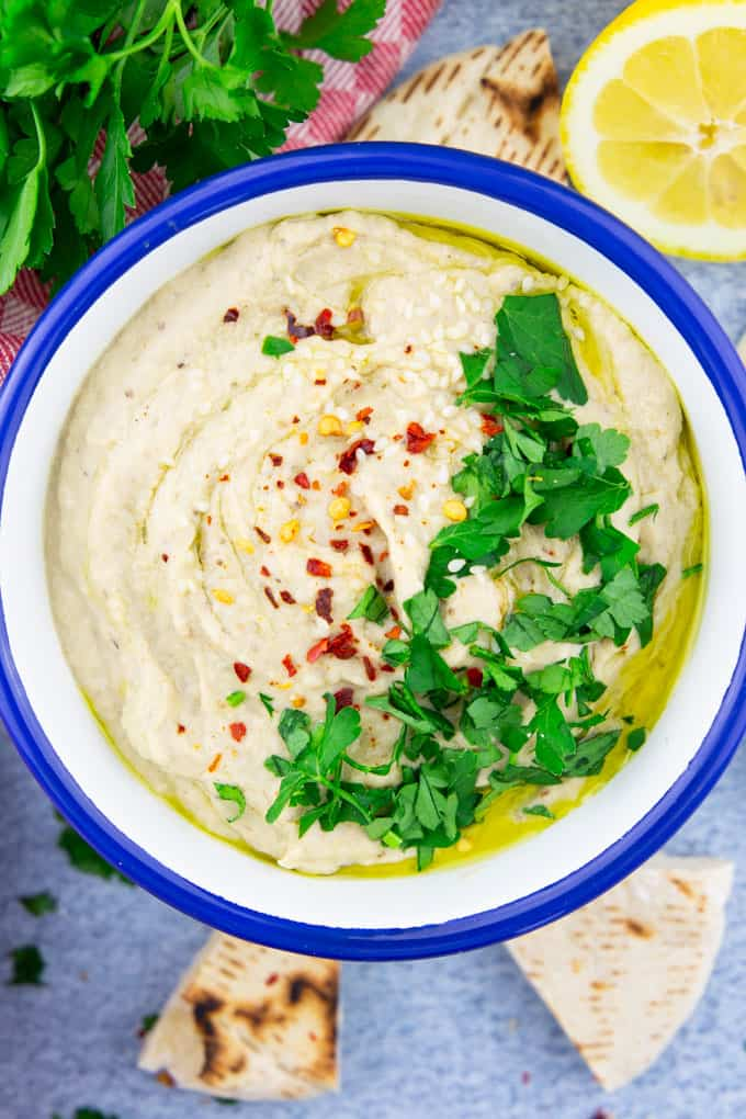 a bowl of Baba Ganoush on a blue counter top with pita slices, parsley, and a lemon half on the side