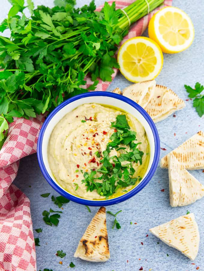 Baba Ganoush in a white and blue bowl on a blue counter top with pita bread, two lemon halves, and fresh parsley on the side