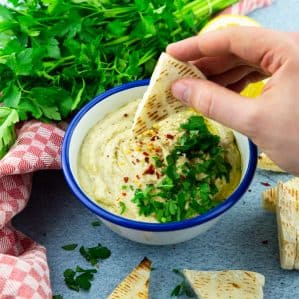 Baba Ganoush in a white and blue bowl on a blue counter top with parsley in the background and a hand dipping a pita into the Baba Ganoush