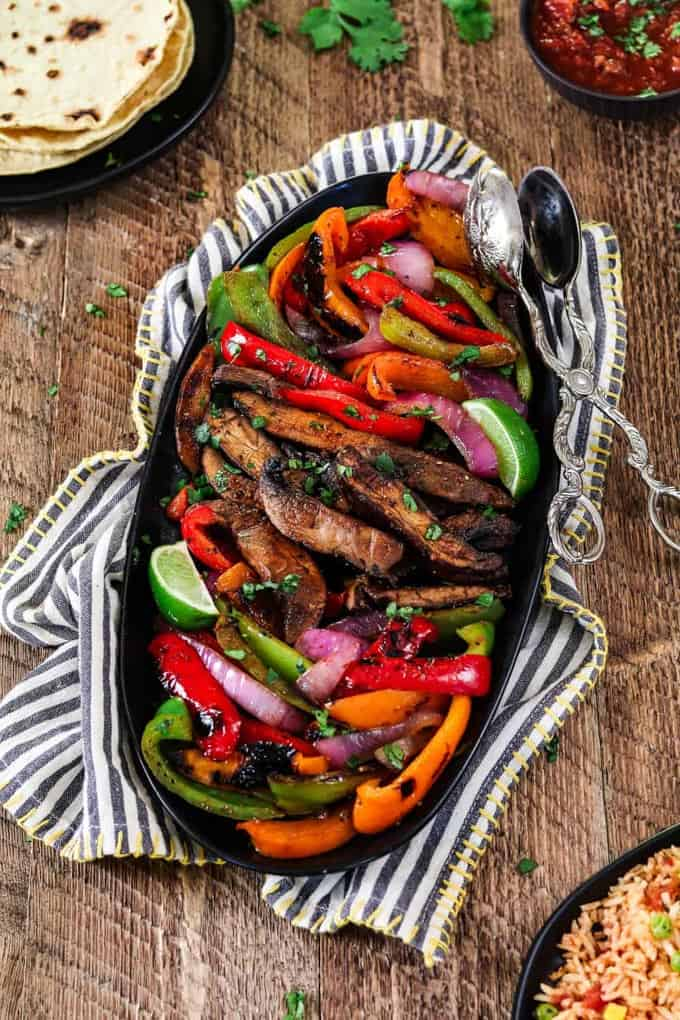 Portobello Vegan Fajitas in a black bowl on a wooden counter top with cooking tongs on the side