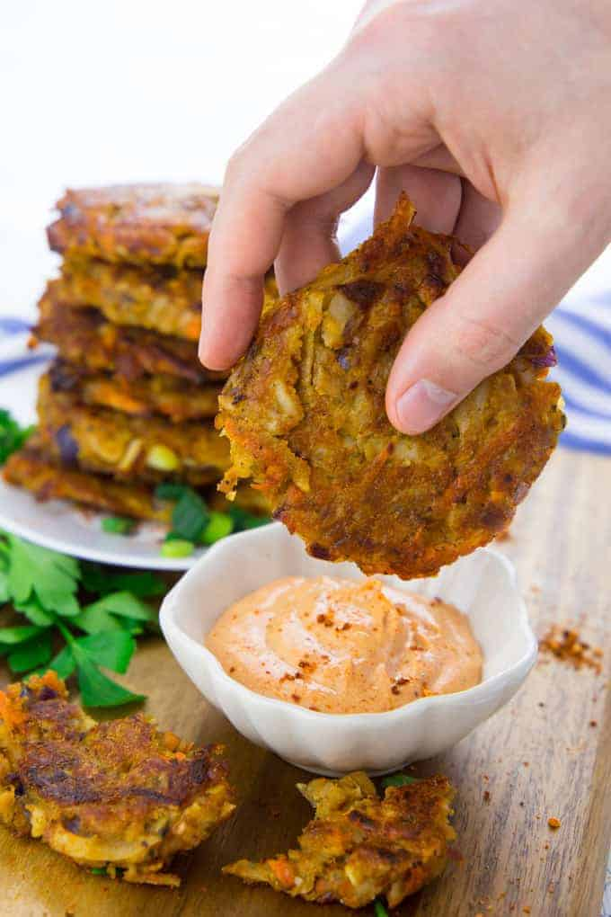 a hand is dipping a vegetable potato fritter into a small bowl of sriracha mayonnaise with more fritters in the background