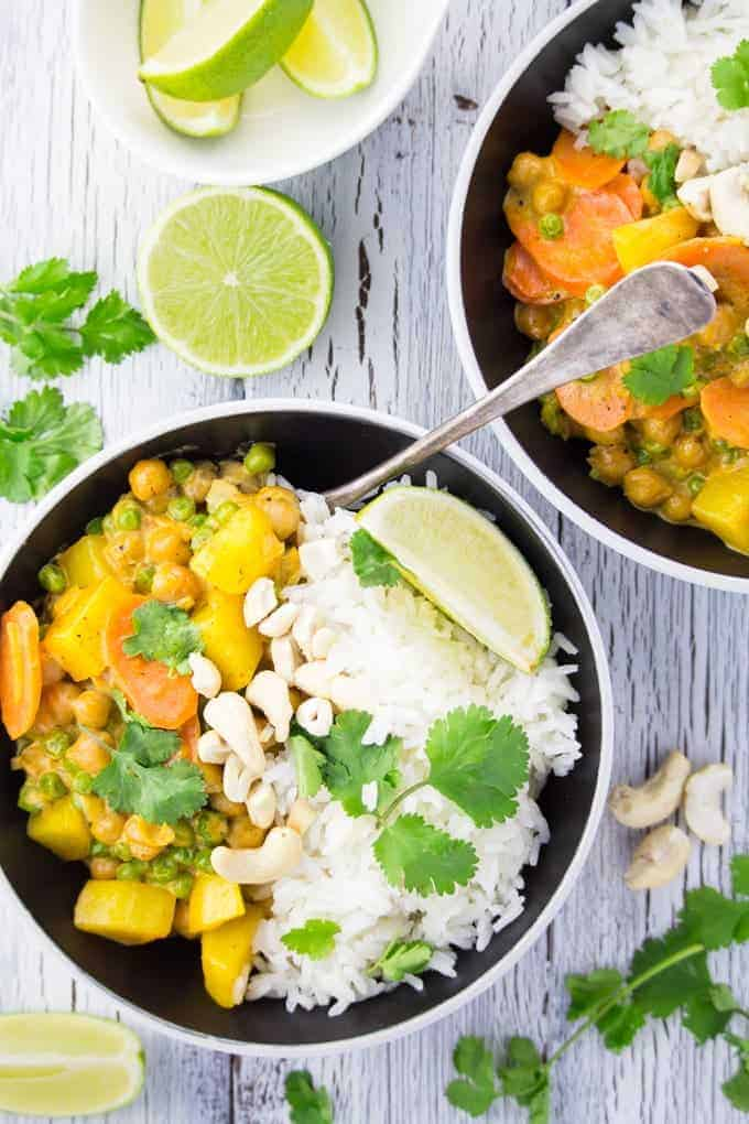 two bowls with vegan chickpea curry with basmati rice in black bowls on a white wooden counter top with cilantro and lime wedges on the side