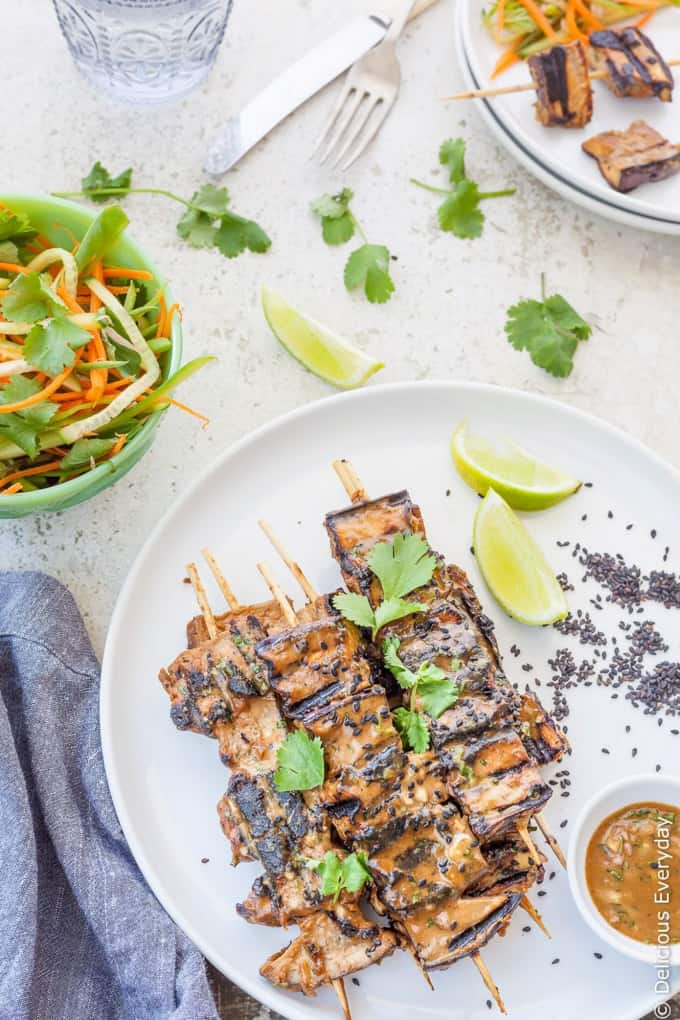 Three Grilled Eggplant Tahini Satay Kebabs on a white plate with lime wedges and peanut sauce on the side