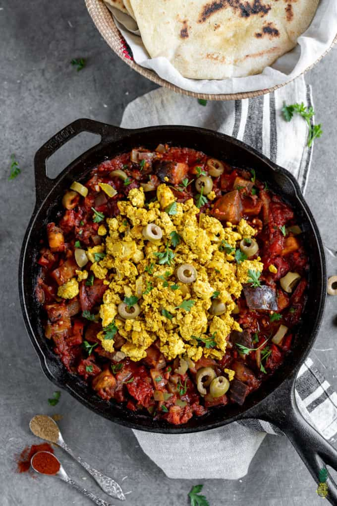 Vegan Eggplant Shakshuka with Tofu Scramble in a cast iron skillet on a concrete counter top