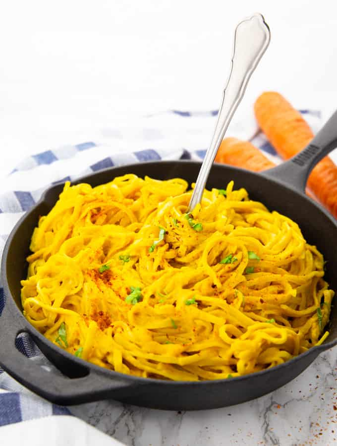 carrot pasta in a cast iron skillet with a fork on a marble counter top with two carrots in the background