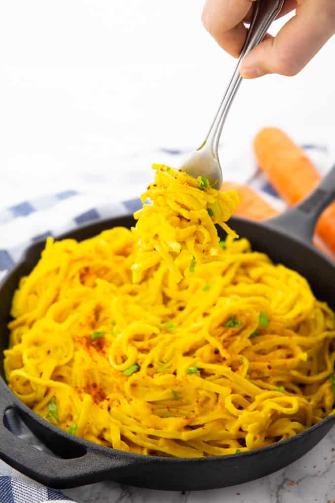 Carrot Pasta in a cast iron skillet with a hand holding a fork with pasta over the skillet