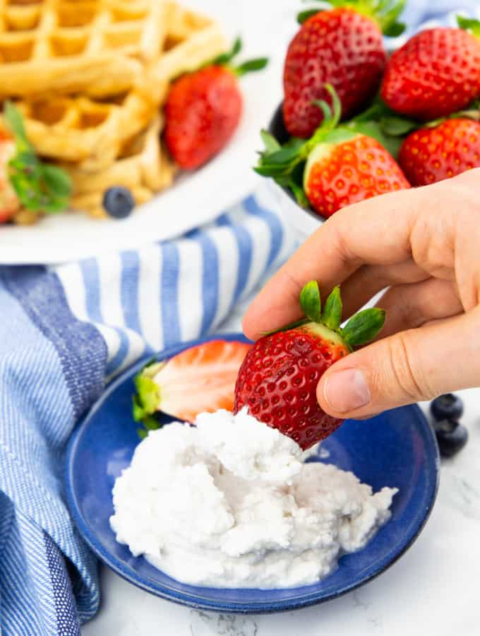 Vegan Coconut Cream on a blue plate with a hand dipping a strawberry into the whipped cream and waffles in the background