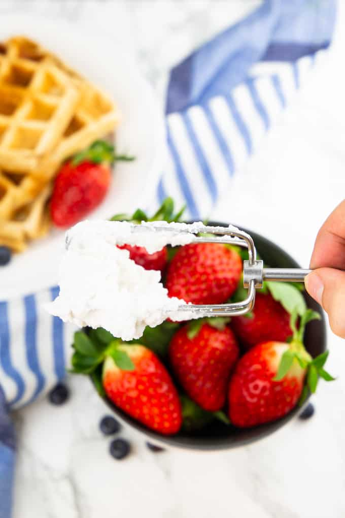 a hand holding a hand mixer with whipped coconut cream over a bowl with strawberries