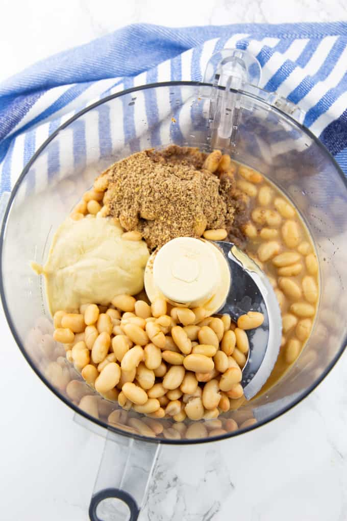 ingredients for a vegan cookie dough dip in a food processor before blending (white beans, nut butter, maple syrup, and flaxseeds)