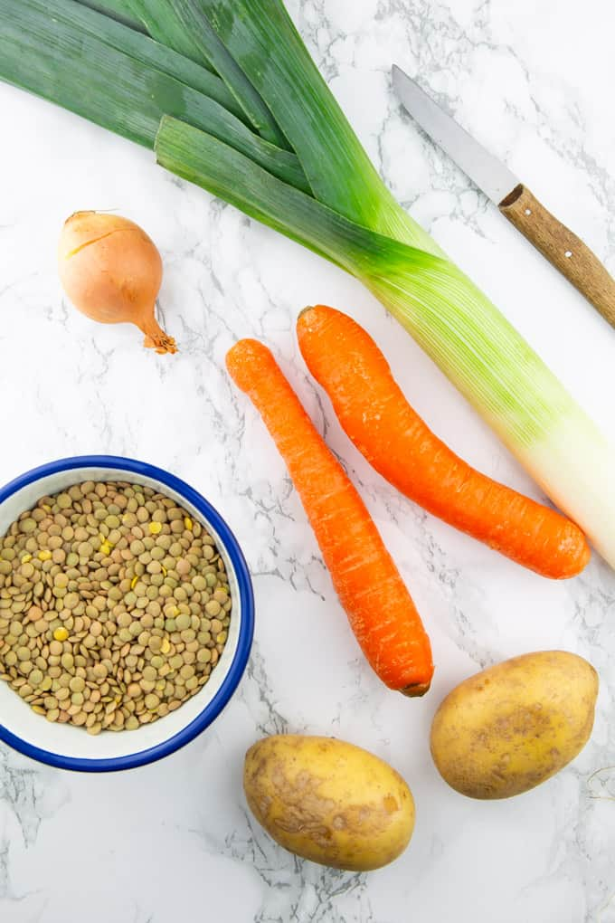 a stalk of leek, two carrots, two potatoes, an onion, and a bowl of lentils on a marble counter top