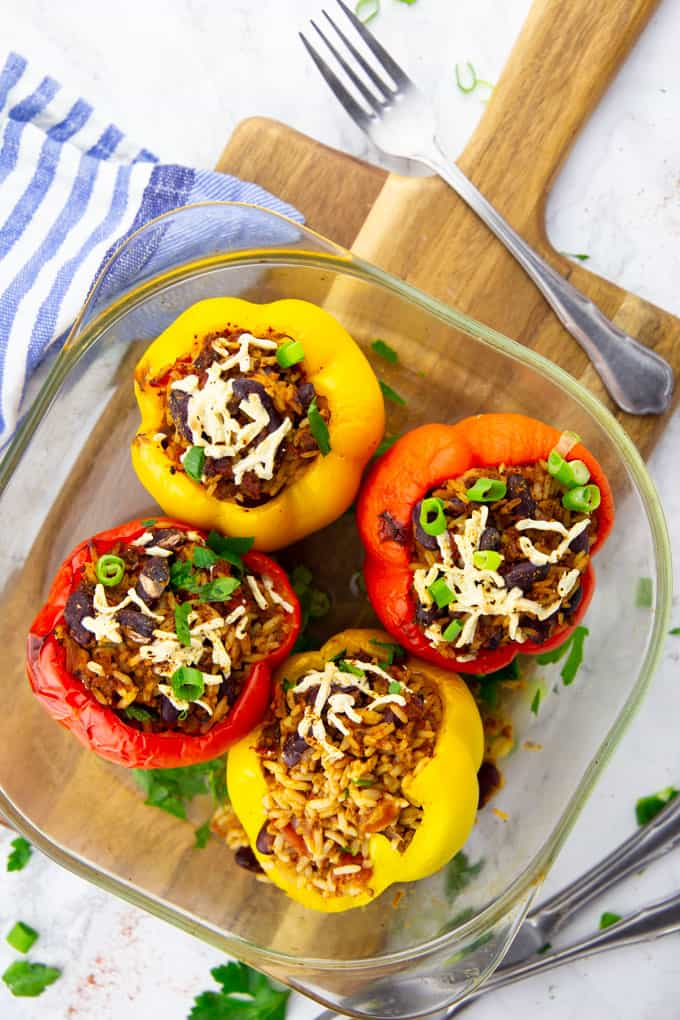Four Vegan Stuffed Peppers in a glass baking dish on a wooden board with cutlery on the side