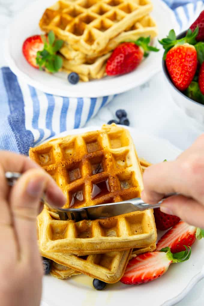 two stacks of vegan waffles on white plates with two hands holding a fork and a knife