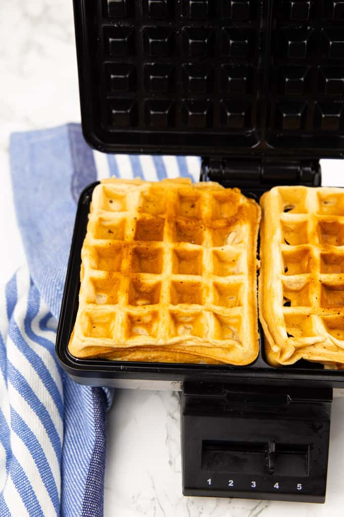 Two crispy and golden vegan waffles in a waffle maker on a marble counter top