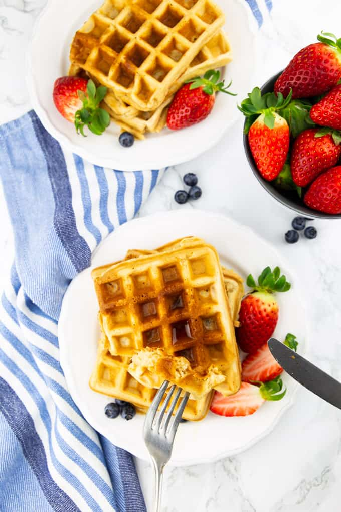 two plates of waffles on a marble countertop with berries on the side
