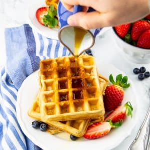 a stack of three vegan waffles on a white plate with a hand pouring maple syrup out of a blue can over the waffles