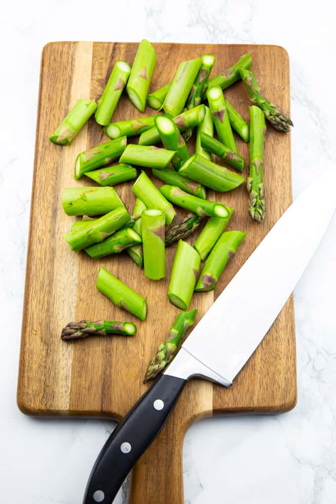 green asparagus cut in pieces on a wooden cutting board with a large knife on the side