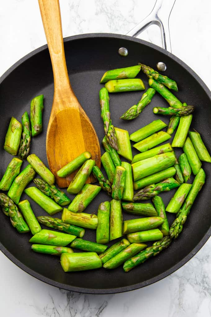 green asparagus cut in pieces in a black pan with a wooden spoon on a marble counter top