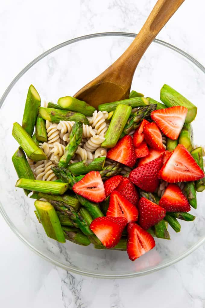 green asparagus pieces, strawberries, and pasta in a glass bowl with a wooden spoon on a wooden countertop