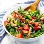 Asparagus Pasta Salad in a white bowl with a wooden spoon on a marble countertop