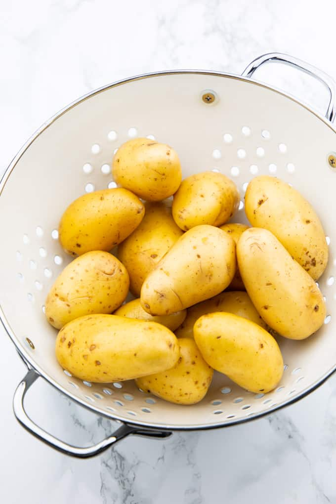 raw potatoes in a white colander on a marble countertop