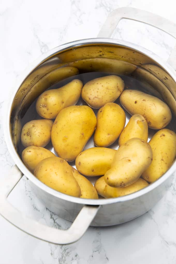 potatoes in a pot with water on a marble countertop