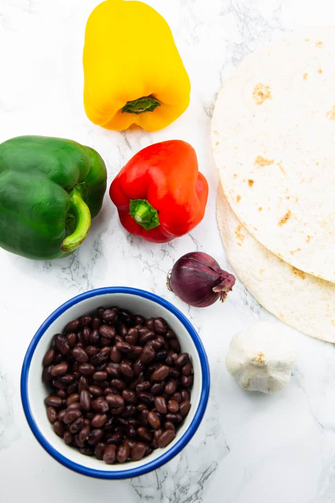 three bell peppers, a bowl of black beans, an onion, garlic, and tortillas on a marble countertop