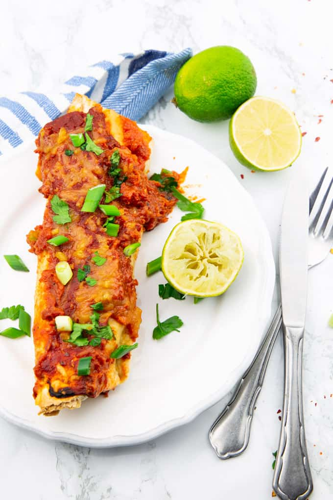a vegan enchilada on a white plate with limes in the background and a knife and a fork on the side