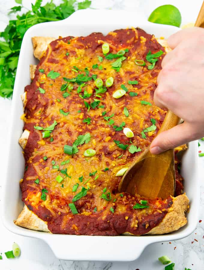 Vegan Enchiladas in a white casserole dish with fresh parsley and limes in the background