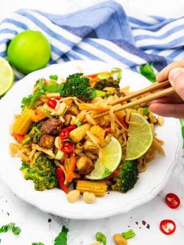 Vegan Pad Thai on a white plate with limes in the background and a hand picking up some noodles with chop sticks