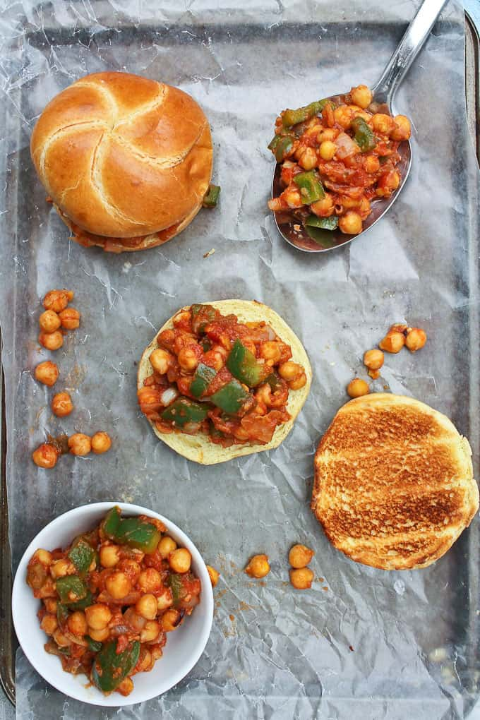 Two Chickpea Sloppy Joes on a baking sheet lined with parchment paper with a spoon and a bowl of the filling on the side