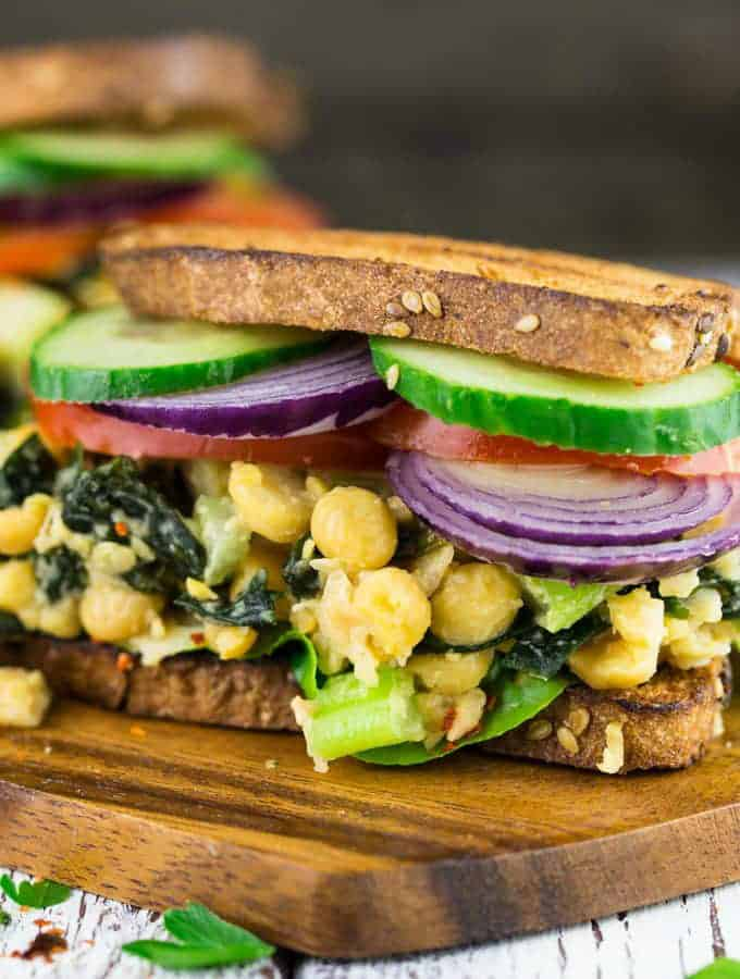 two vegan tuna sandwiches with chickpeas on a wooden board with a grey background