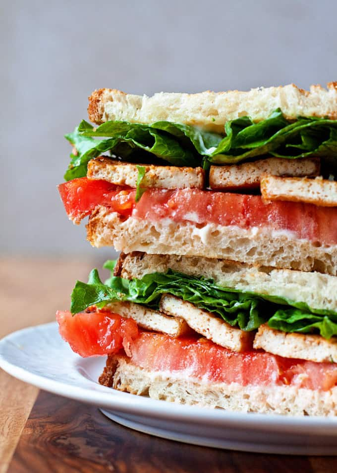 a stack of tofu lettuce tomato sandwiches on a white plate