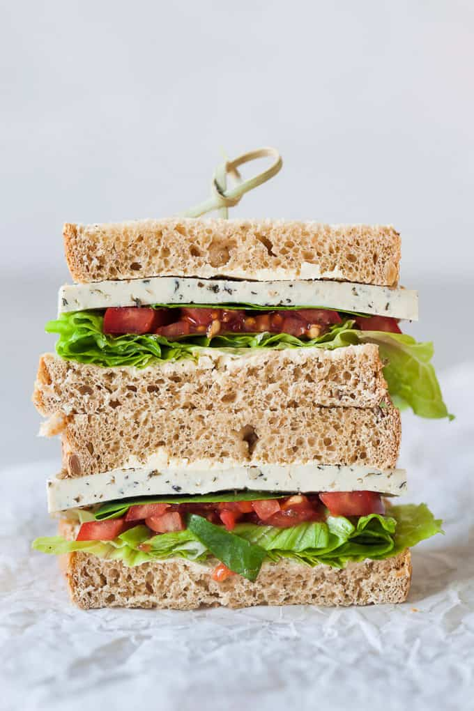 a stack of two basil tofu tomato vegan sandwiches with a white background