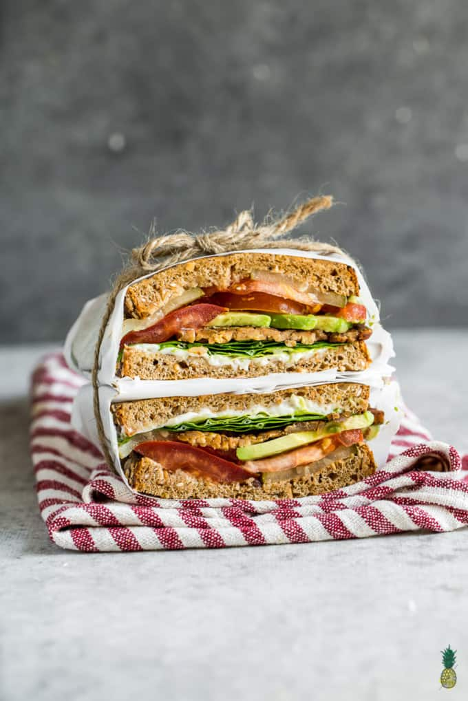 a stack of homemade vegan sandwiches with tempeh, lettuce, and tomato wrapped in parchment paper