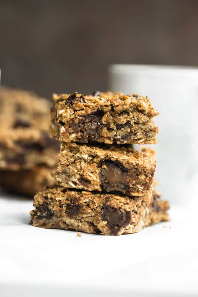 a pile of three vegan granola bars with a white mug in the background