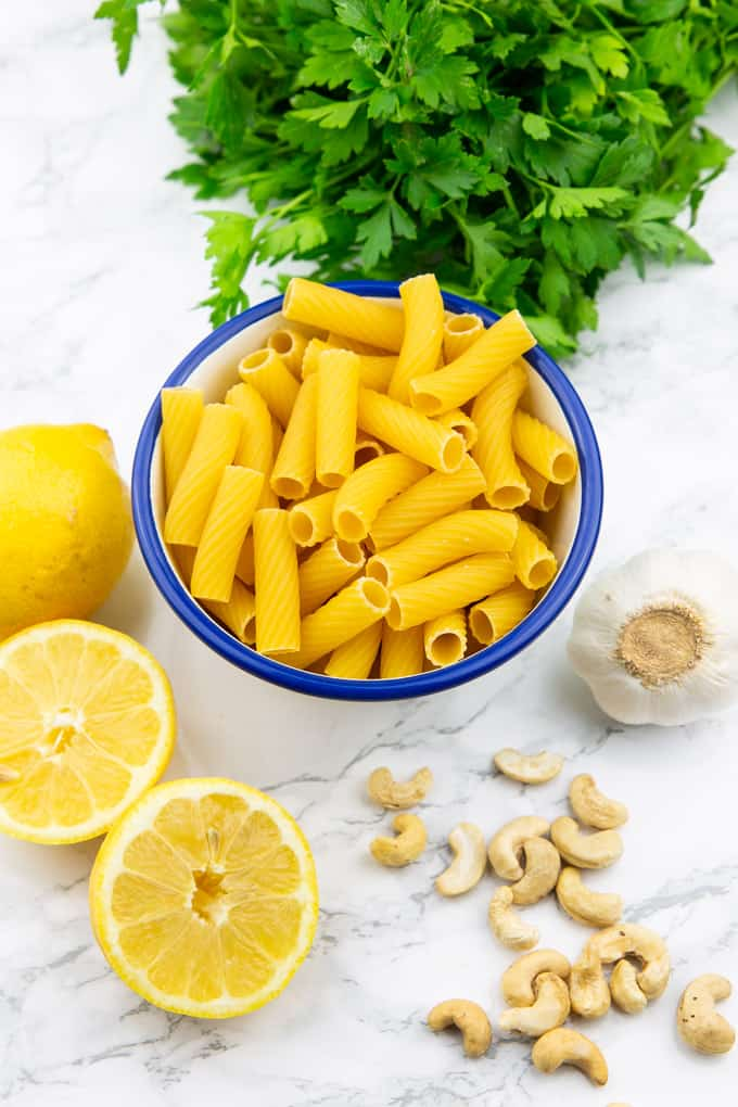 a small bowl with rigatoni, a bunch of parsley, two lemons, garlic, and cashews on a marble countertop