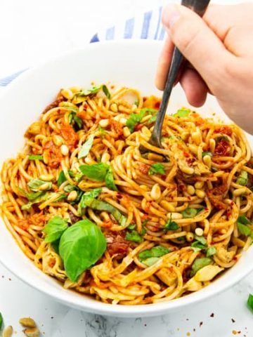 Pesto Pasta Salad in a white bowl with a hand rolling up some of the spaghetti with a fork
