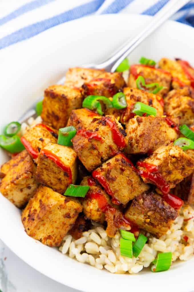 close-up photo of marinated tofu with brown rice in a white bowl