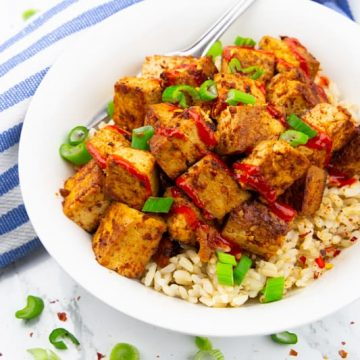Marinated Tofu over brown rice sprinkled with chopped green onions in a white plate on a marble countertop