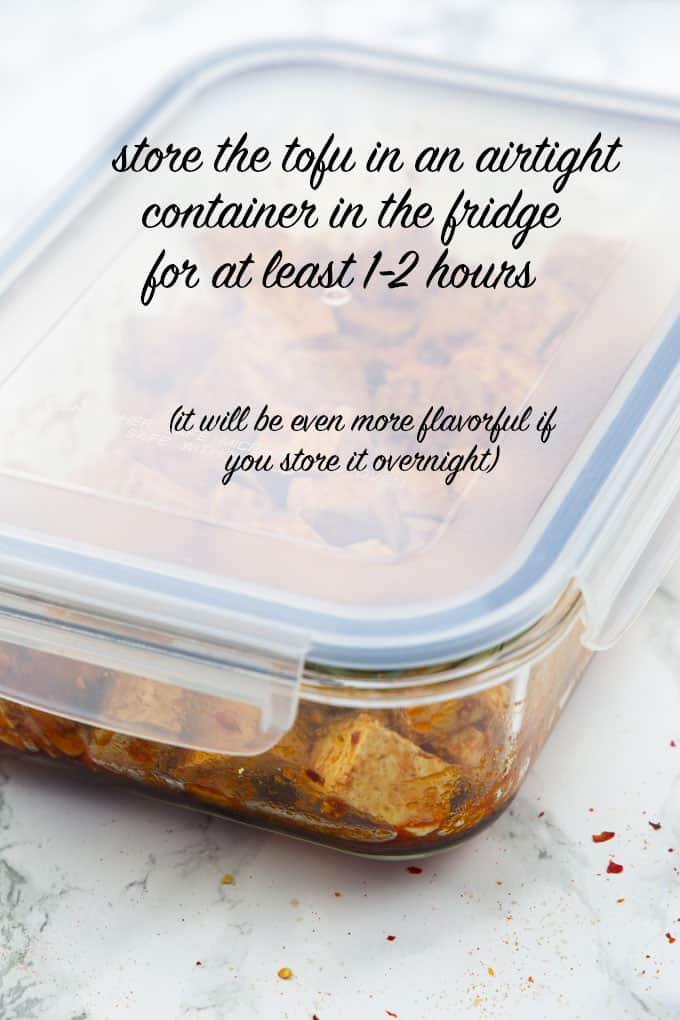 "a food container with tofu marinade and cubed tofu on a marble countertop with the writing ""store the tofu in an airtight container in the fridge for at least 1-2 hours"" on top"