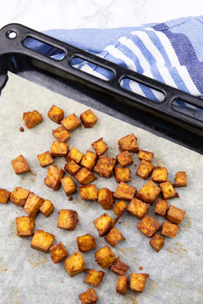 crispy baked tofu cubes on a baking sheet lined with parchment paper