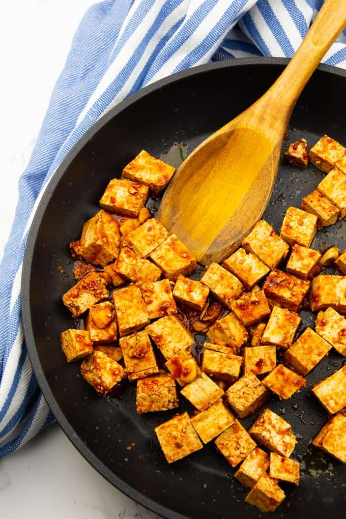 marinated tofu cubes in a cast iron skillet with a wooden spoon on a marble countertop