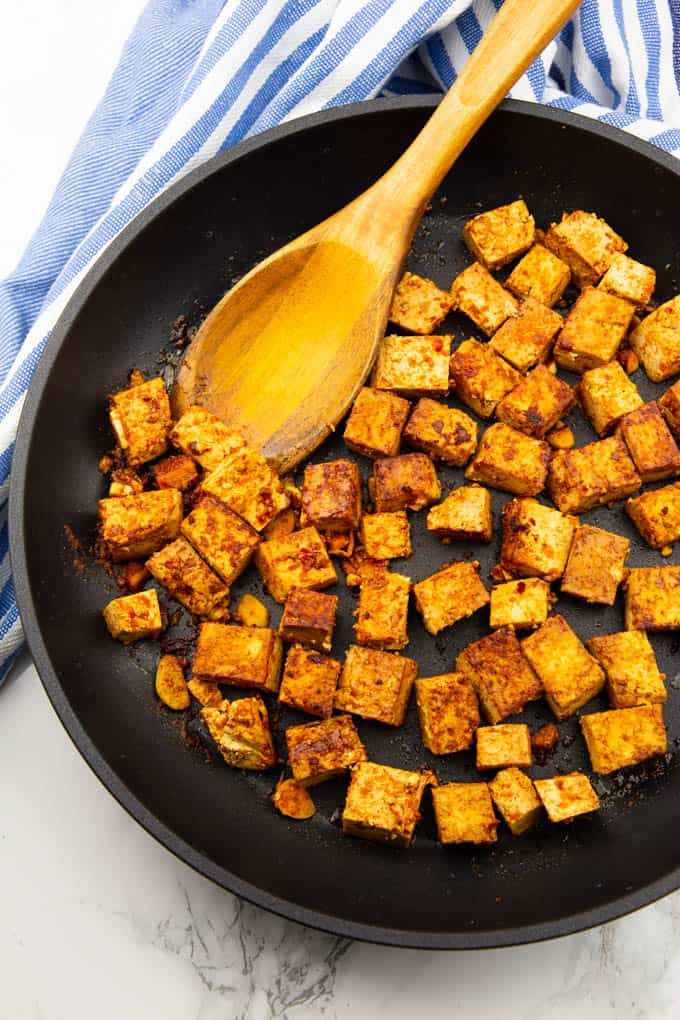 tofu cubes in a cast iron skillet with a wooden spoon on a marble countertop