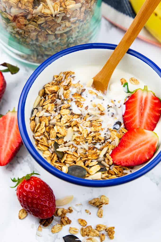 Vegan Cereal with yogurt and strawberries in a blue and white bowl on a marble countertop