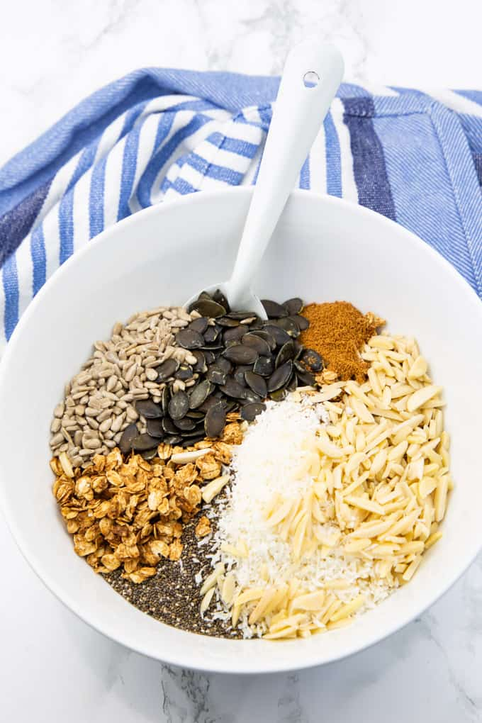Vegan Cereal with almonds, pumpkin seeds, sunflower seeds, chia seeds, and coconut sugar in a white bowl on a marble countertop with a blue tablecloth in the background