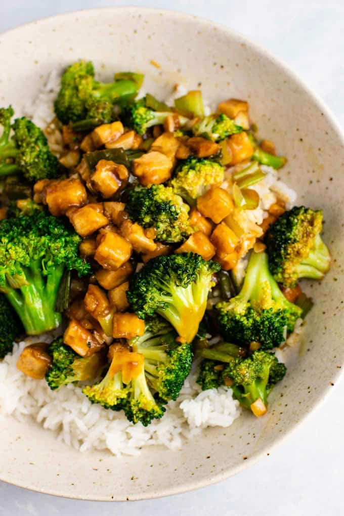 Broccoli Tofu Stir Fry served over basmati rice in a white bowl on a white countertop