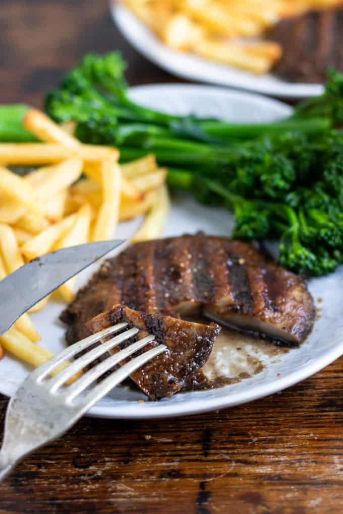 a portobello mushroom steak with French fries and broccoli in the background on a white plate on a wooden countertop