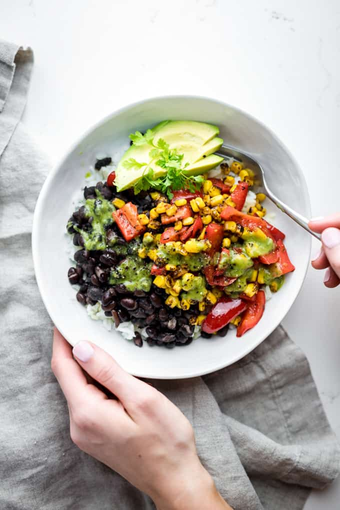 a vegan burrito bowl with black beans and avocado in a white bowl with two hands holding a fork on a white countertop